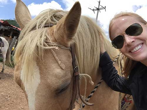 Darley Newman rides a horse in Tapalpa Mexico