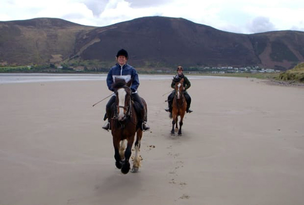 Horseback riding on Rossbeigh Beach in Ireland.